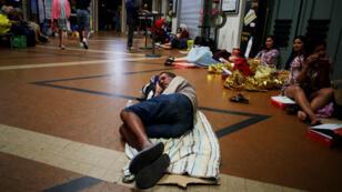 Un homme dort sur le carrelage de la gare SNCF de Lisieux, en Normandie, le 7 août 2018.