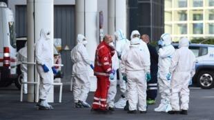عاملون صحيون من الصليب الأحمر الإيطالي في ميناء جنوى قرب سفينة كوستا لومينوزا التي تحمل ركابا مصابين بفيروس كورونا. 21 مارس/آذار 2020.