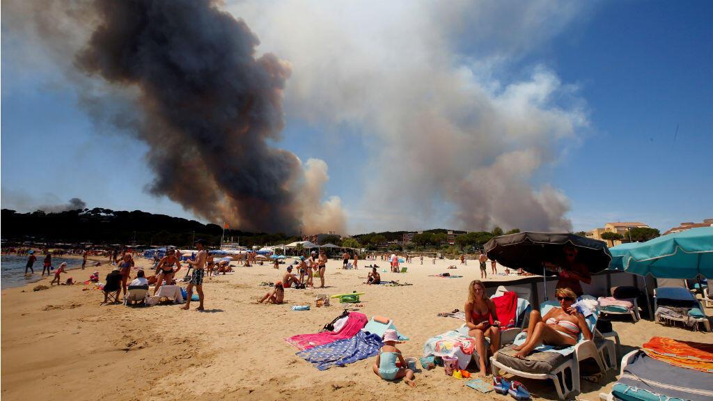 Esta imagen es particular, retrata la indiferencia de algunas personas. El humo llena el cielo sobre una montaña en llamas mientras los turistas se relajan en unas playas en Francia.