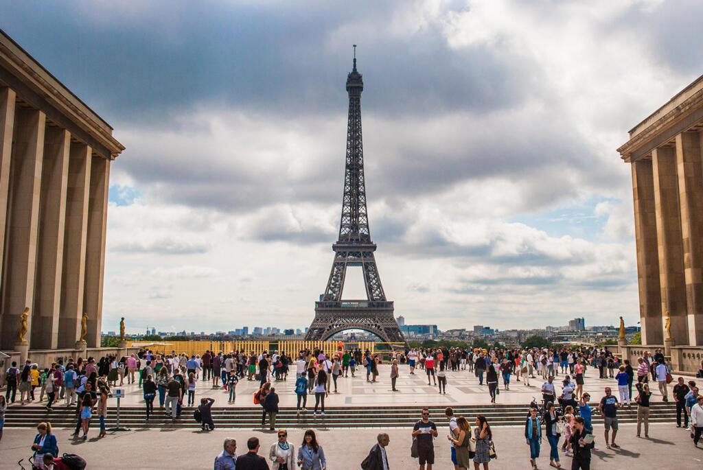Turistan contemplan la Torre Eiffel, en París, Francia, uno de los monumentos más visitados del planeta.