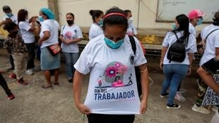 """Un trabajadora de la salud muestra una camiseta que reza 'Día del Trabajador' durante una marcha en Caracas, Venezuela, donde distintos gremios exigieron salarios """"dignos"""" y vacunación masiva contra el Covid-19."""