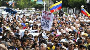 Des militants d'opposition écoutent le président de l'Assemblée nationale, Juan Guaido, à Caracas, le 11 janvier 2019.
