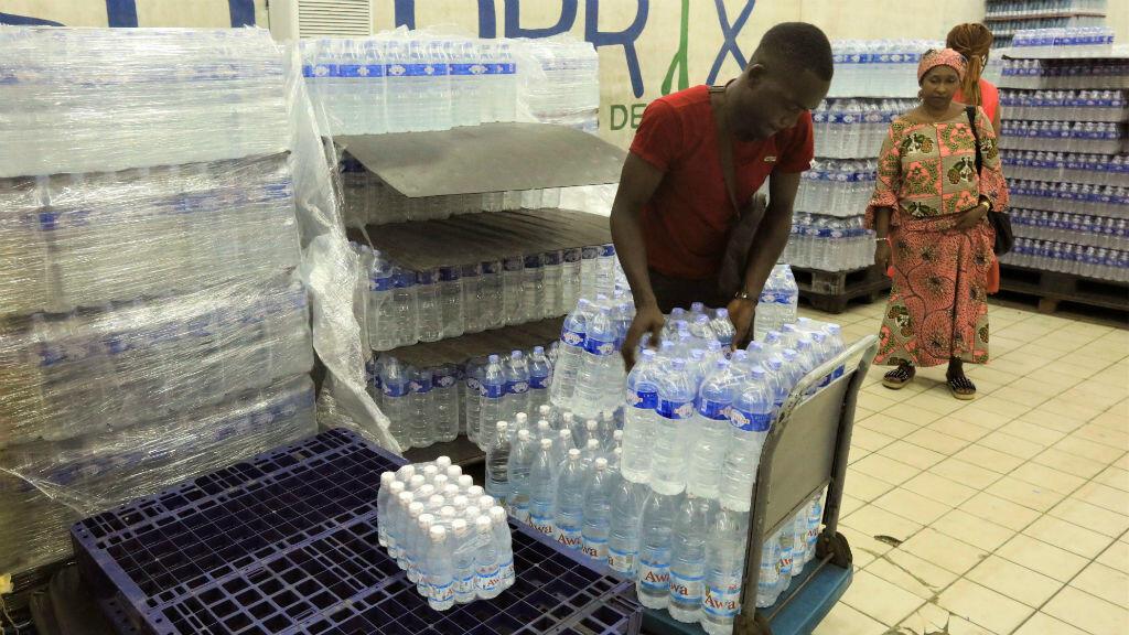 Un trabajador distribuye botellas de agua en un supermercado de Abiyán, en Costa de Marfil, este 18 de marzo de 2020.
