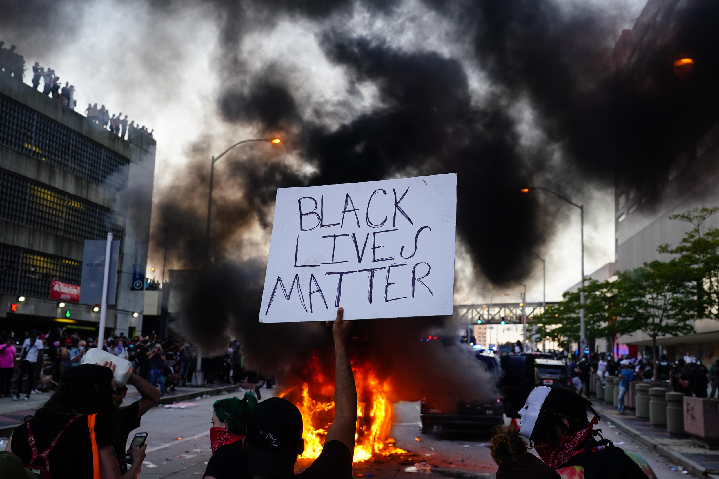 A man holds a Black Lives Matter sign as a police car burns during a protest on May 29, 2020 in Atlanta, Georgia.