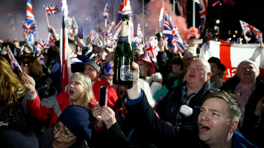Un hombre levanta una botella de champán mientras la gente celebra que Gran Bretaña abandonó la UE en Londres, Gran Bretaña, el 31 de enero de 2020.