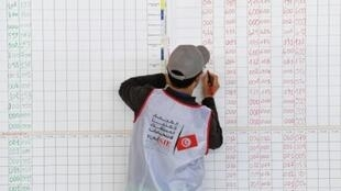 عضو في الهيئة المكلفة بتنظيم الانتخابات البلدية في تونس يحصي النتائج، 7 أيار/مايو 2018