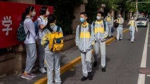 Unos alumnos salen de un colegio de enseñanza secundaria de Pekín el 11 de mayo de 2020