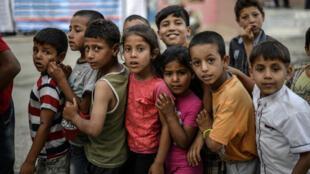 Des enfants syriens font la queue pour manger, à Akçakale, en Turquie, le 20 juin 2015.