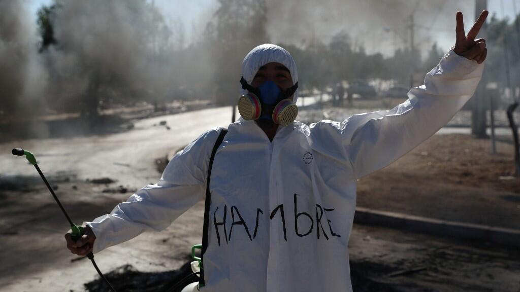 Un manifestante usa un traje protector que dice 'Hambre' durante un enfrentamiento con la policía antidisturbios en un barrio pobre, durante una protesta para solicitar paquetes de alimentos al Gobierno en medio de la cuarentena, por el Covid-19. En  'Puente Área de Alto, Santiago, Chile, el 25 de mayo de 2020.