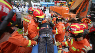 Rescue workers move a casualty at the site where a hotel being used for a coronavirus quarantine collapsed in the southeastern Chinese port city of Quanzhou in Fujian province on March 8, 2020.