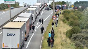 La police veille le long de la rocade à empêcher les migrants de grimper dans les camions.