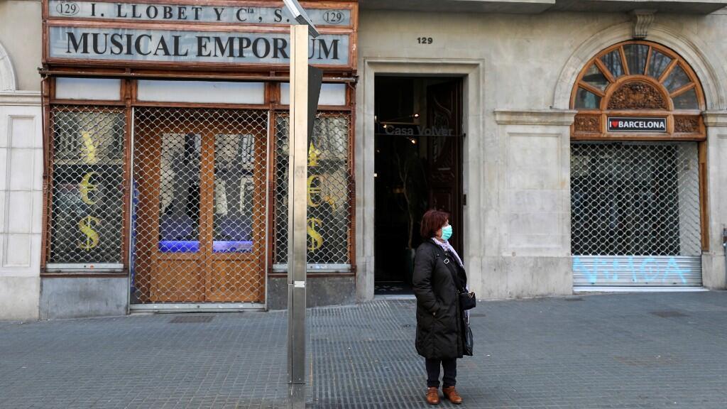 Una mujer usa una máscara facial protectora mientras espera el autobús en una parada vacía, en medio de la preocupación por el brote de coronavirus en España, en Barcelona, España, el 14 de marzo de 2020.