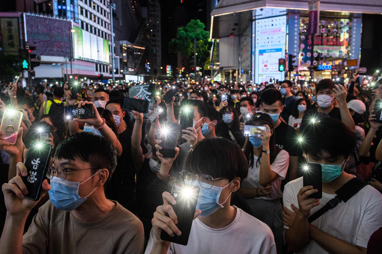 Activistas prodemocracia de Hong Kong sostienen sus teléfonos móviles durante un acto de protesta en junio.