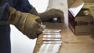 Un trabajador sanitario realiza unos tests rápidos de antígenos el 13 de julio de 2020 en la ciudad india de Ahmedabad