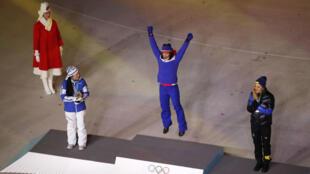 La medallista de oro Marit Bjoergen de Noruega celebra en el podio entre la medallista de plata Krista Parmakoski de Finlandia y la medallista de bronce Stina Nilsson de Suecia, durante la ceremonia de clausura de los Juegos Olímpicos de Invierno 2018 en Pyeongchang, el 25 de febrero de 2018.
