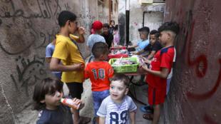 أطفال فلسطينيون يتجمعون في شارع في مخيم الأمعري في الضفة الغربية حول بائع جوال في 29 تموز/يوليو 2020