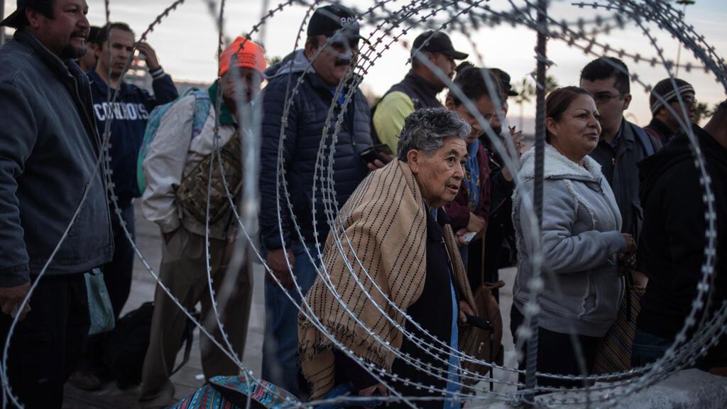 Una concertina se muestra imponente mientras la gente espera en la fila en el puerto de entrada de San Ysidro después de que el cruce de la frontera terrestre se cerrara temporalmente al tráfico desde Tijuana, México, 19 de noviembre de 2018.