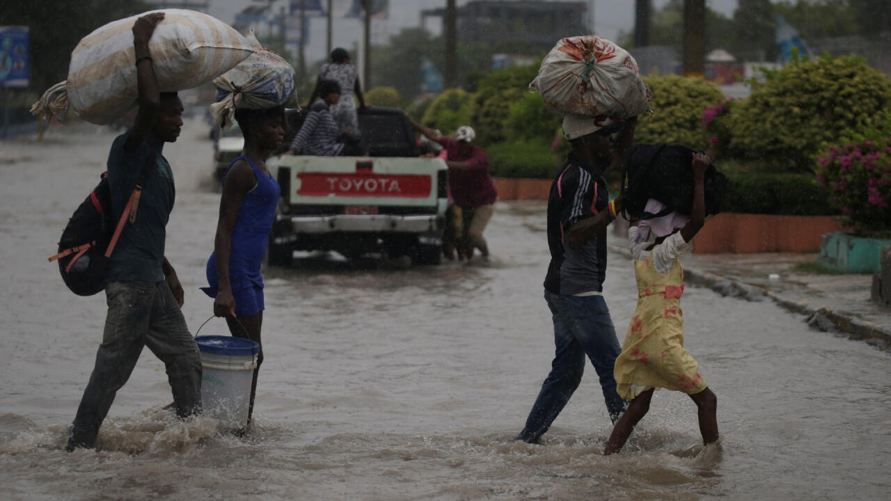 Personas cruzan una calle inundada durante el paso de la tormenta Laura, en Port-au-Prince, Haití, el 23 de agosto de 2020.