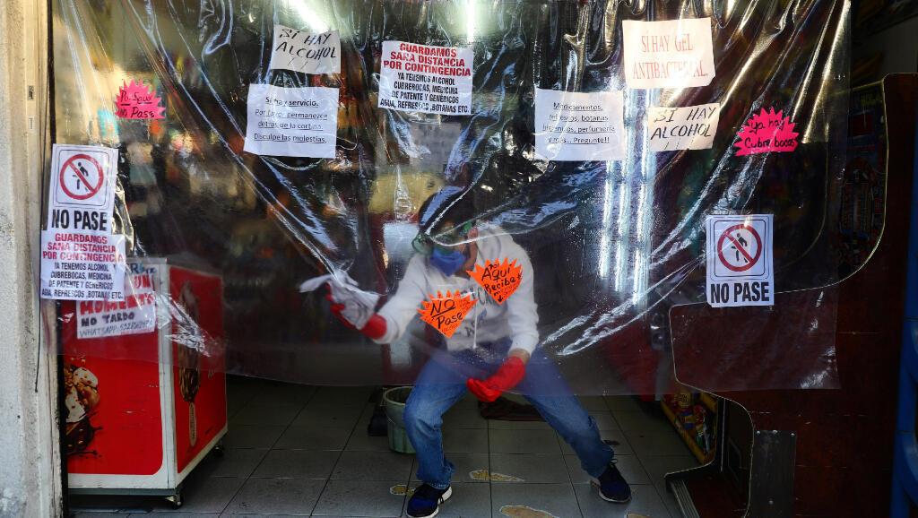 Esta hombre desinfecta el plástico con el que cubre su negocio en Ciudad de México durante la pandemia por Covid-19, el 3 de mayo de 2020.