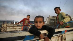 Los niños se paran en la parte trasera de un camión mientras huyen de la ciudad de Ras al Ain, Siria, 9 de octubre de 2019.