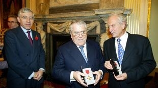 Albert Roux (C) and his brother Michel (R) receive their honorary OBE medals at the Foreign Office in London on October 31, 2002.