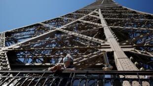 احد زوار برج ايفل يضع كمامة ويتأمل منظر باريس في 25 حزيران/يونيو 2020.