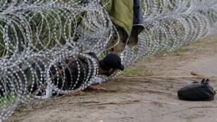 Une personne traverse une clôture de fils barbelés à la frontière serbo-hongroise, le 26 août 2015.
