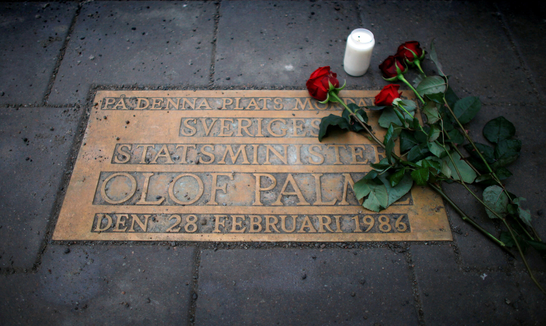 Roses lie on a plaque marking the location where Swedish Prime Minister Olof Palme was shot and killed on a Stockholm street in 1986.