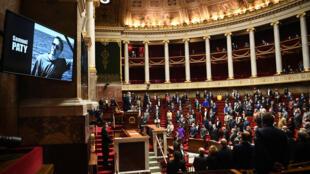 برلمانيون فرنسيون يقفون دقيقة صمت حداداً على المدرس صامويل باتي الذي قتل ذبحاً قرب مدرسته لعرضه على تلامذته رسوماً كاريكاتورية تمثّل النبي محمد، وذلك في مستهل جلسة لمساءلة الحكومة في مقرّ الجمعية العامة في باريس في 20 ت1/أكتوبر 2020.