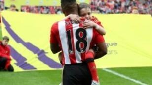 الطفل برادلي لاوري بين أيدي المهاجم جرماين ديفو قبيل مباراة سندرلاند وسوانزي في 13 أيار/مايو 2017