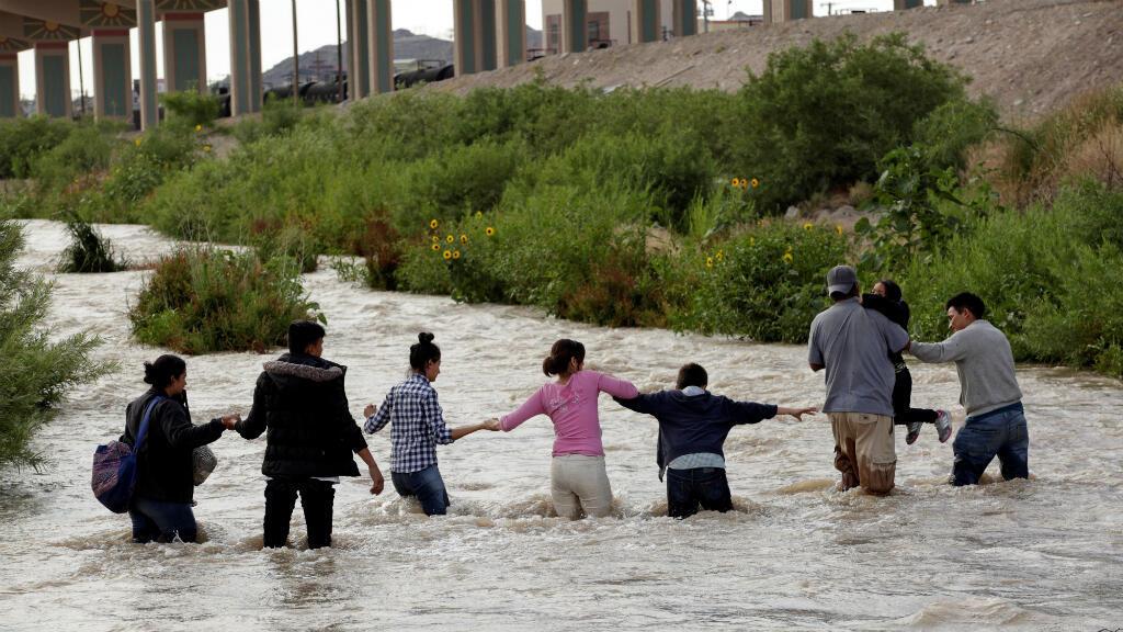 Migrantes centroamérica forman una cadena humana para cruzar el río Bravo para ingresar ilegalmente a Estados Unidos para solicitar  asilo en El Paso, Texas, EE. UU. Ciudad Juárez, México, el 11 de junio de 2019.