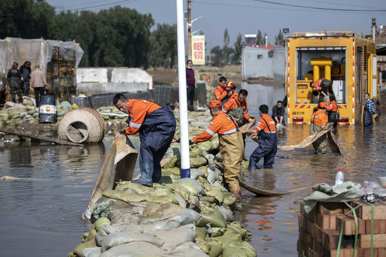 Operarios de rescate tratan de drenar el agua de una zona inundada en la ciudad de Jinzhong en la provincia china de Shanxi, el 11 de octubre de 2011