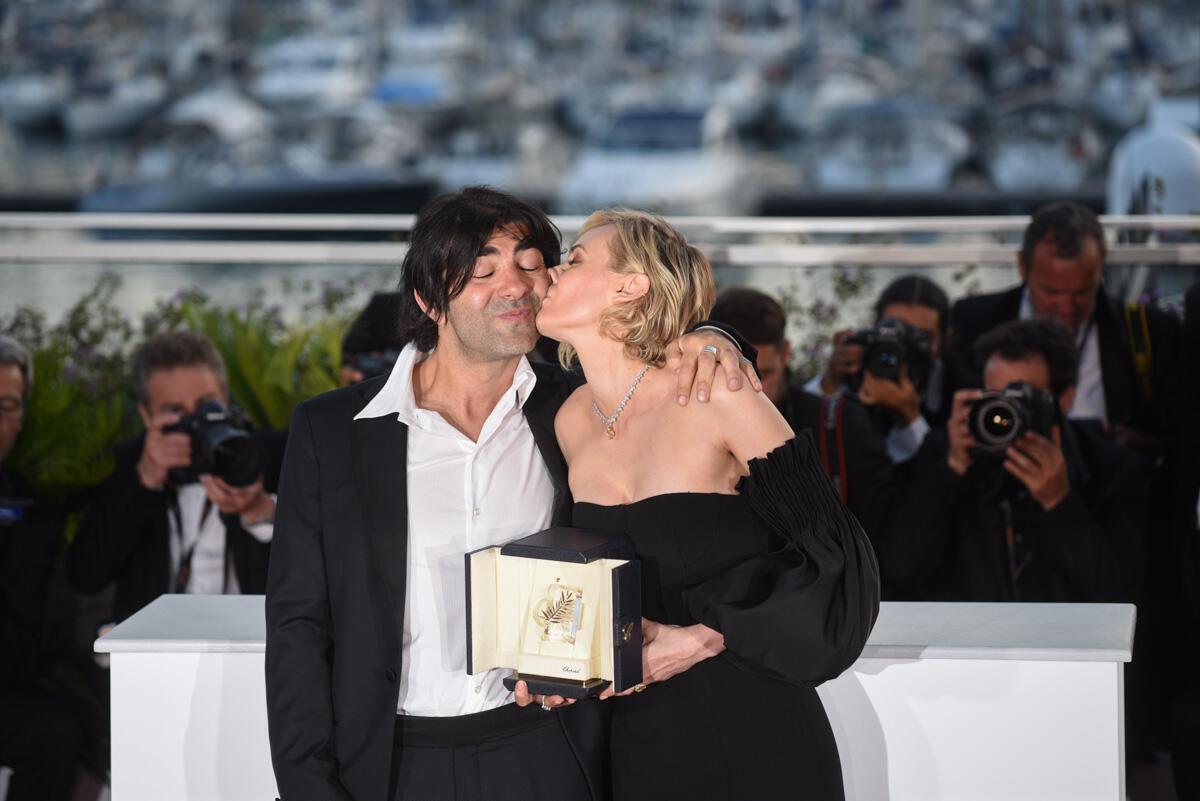 """L'actrice allemande Diane Kruger embrasse le réalisateur Fatih Akin après avoir remporté le prix d'interprétation féminine pour son rôle dans """"In the fade"""". Elle y joue le rôle d'une veuve allemande cherchant à venger le meurtre de son mari d'origine turque dans un attentat néonazi."""