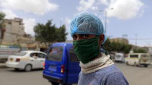 Un hombre con mascarilla y gorro capilar por el coronavirus posa para la cámara el 28 de marzo de 2020 en una calle de Saná, la capital yemení