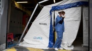 Un membre du personnel hospitalier ajuste son masque de protection à l'hôpital Henri Mondor de Créteil, le 6 mars 2020.
