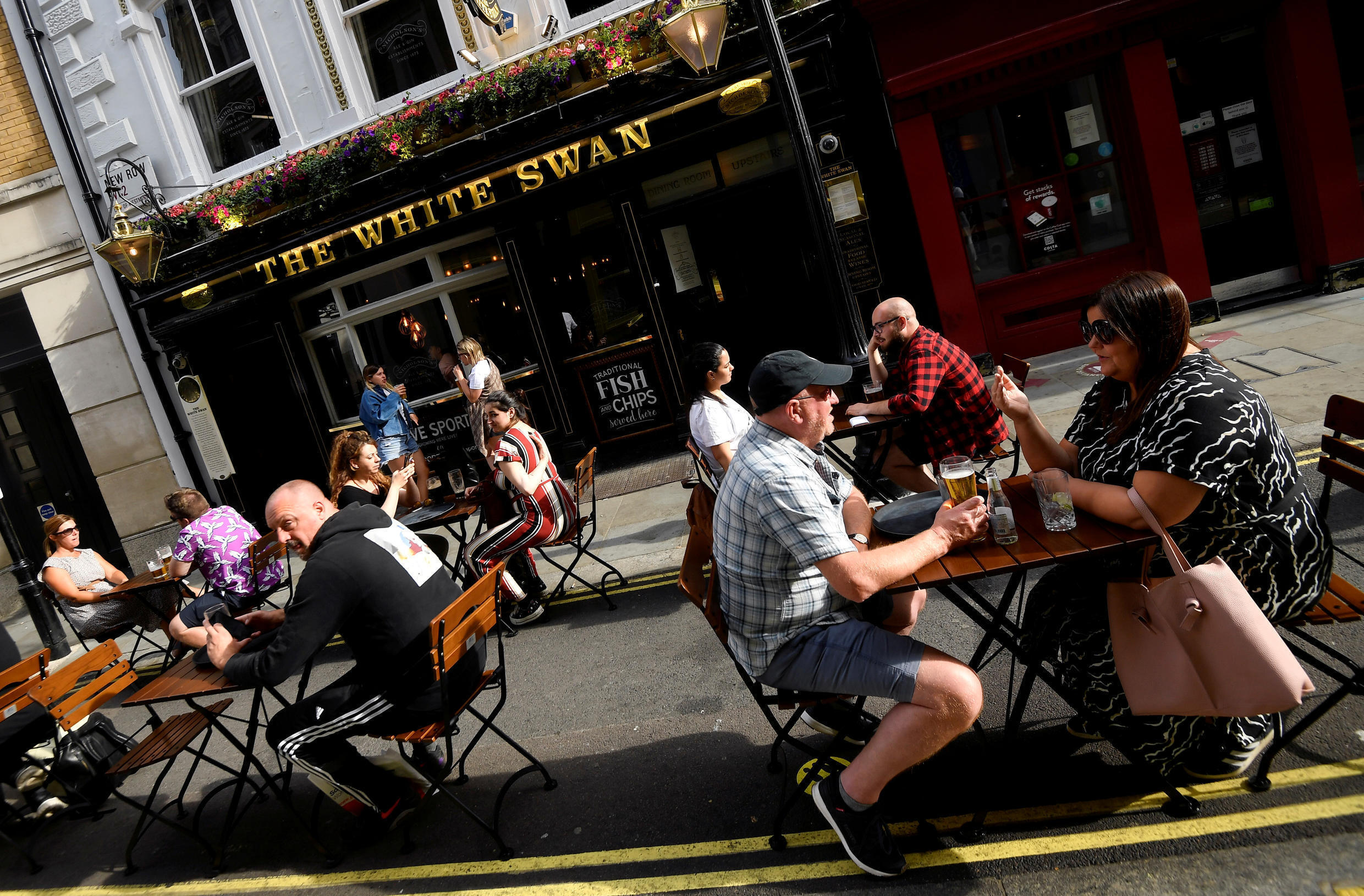 People drink outside a pub at the Covent Garden shopping and dining district, amid the spread of the coronavirus disease (COVID-19), in London, Britain, August 2, 2020.