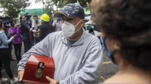 El residente Carlos Rodríguez Delgado sostiene una caja con las cenizas de su madre en el exterior de un edificio de apartamentos después de que fuera evacuado debido a los daños causados por un terremoto en la Ciudad de México el 24 de junio de 2020, en medio de la nueva pandemia de coronavirus.