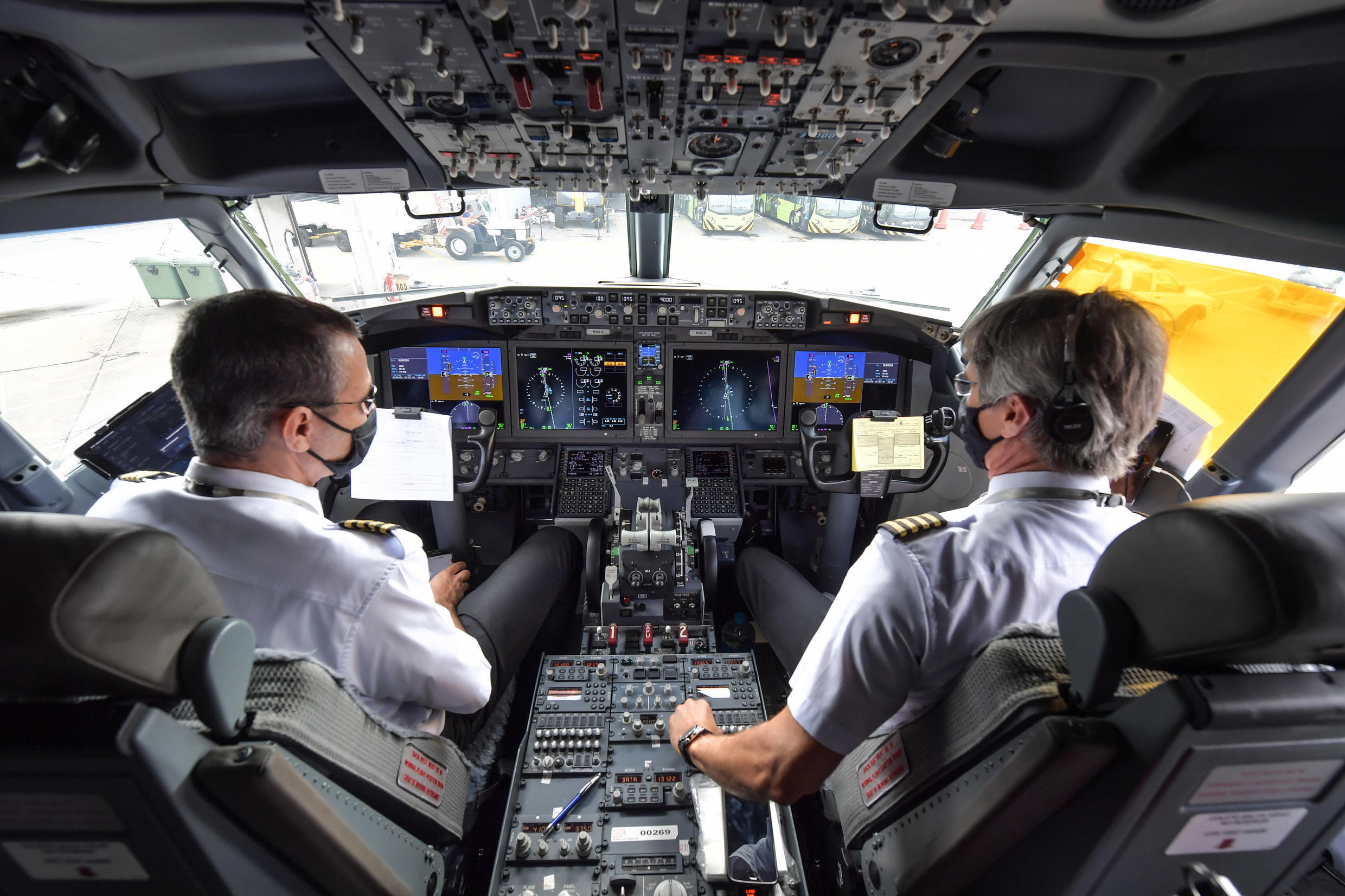 Pilots are pictured in the cockpit of a Boeing 737 MAX aircraft operated by low-cost airline Gol as it sits on the tarmac before take off at Guarulhos International Airport, near Sao Paulo on December 9, 2020, as the 737 MAX returns into use more than 20 months after it was grounded following two deadly crashes