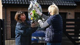 Une fleuriste livre un bouquet de fleurs et de muguet à une cliente, le 30 avril 2020 à La Couture, dans le Pas-de-Calais