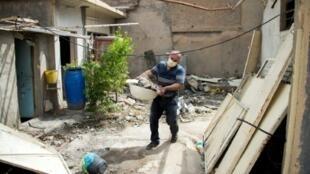 عراقي يتولى ازالة الركام من منزله في قرقوش في 5 ايار/مايو 2017