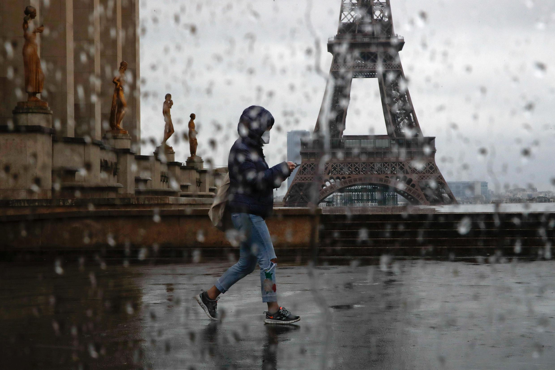 صورة امرأة ترتدي قناعا طبيا تعبر الطريق أمام برج إيفل ساحة تروكاديرو، باريس، فرنسا  6 أبريل/ نيسان 2020