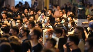 Des manifestants dans le quartier de Wanchai, à HongKong, pendant le discours de la cheffe de l'exécutif, Carrie Lam, le 27septembre2019.