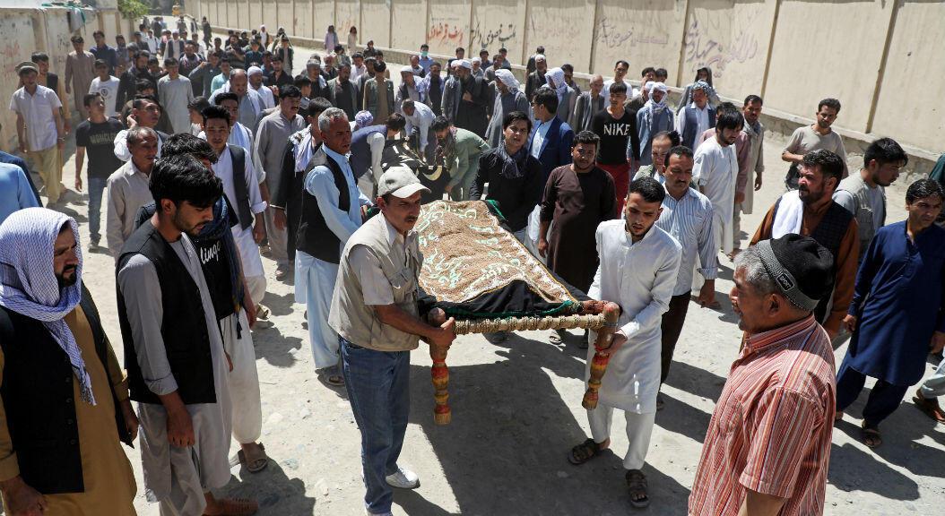 Hombres afganos llevan los cuerpos de las víctimas durante un funeral masivo después de la explosión de una bomba suicida en una boda en Kabul, Afganistán, el 18 de agosto de 2019.