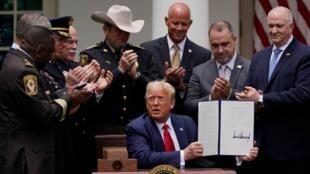 Los funcionarios encargados de hacer cumplir la ley aplauden después de que el presidente Donald Trump firmase una orden ejecutiva sobre la reforma policial, en el Rose Garden de la Casa Blanca, el martes 16 de junio de 2020, en Washington.