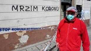 """رجل يضع كمامة يمر من أمام جدار كتب عليه """"أكره كورونا"""" في زغرب بتاريخ 17 نيسان/أبريل 2020"""