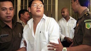 Andrew Chan and Myuran Sukumaran (back), are escorted by Indonesian prison guards after a court hearing in 2006.