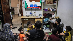 A Palestinian family watches a televised speech by president Mahmud Abbas regarding the upcoming Palestinian elections at their home in the Rafah refugee camp in the Gaza Strip