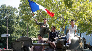 Vehículos militares antiguos y varios participantes durante una recreación de la liberación de París de la ocupación alemana para celebrar su 75 aniversario, en París, Francia, el 25 de agosto de 2019.