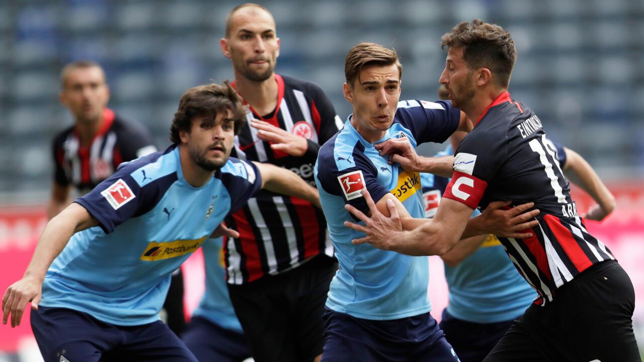 Jugadores del Eintracht Frankfurt (rayas) y del Borussia Moenchengladbach (azul) forcejean en un tiro de esquina durante el partido de este 16 de mayo de 2020 en Frankfurt, Alemania. Los locales perdieron por 1-3.