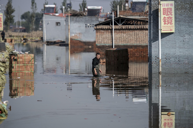 Un hombre camina con el agua hasta la cintura en la ciudad de Jinzhong, en la provincia china de Shanxi (norte), el 11 de octubre de 2021